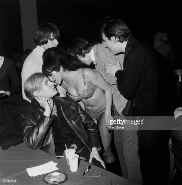 A female gogo dancer whispers into the ear of American Pop Artist Andy Warhol during a Velvet Underground and Nico performance in a 'Freakout' party...