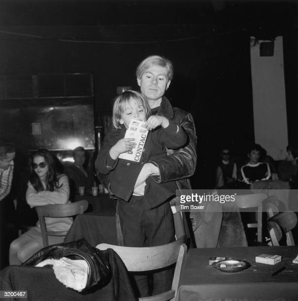 American artist Andy Warhol holds Ari Pffgen son of singer Nico who was performing with the rock group The Velvet Underground during a 'Freakout'...