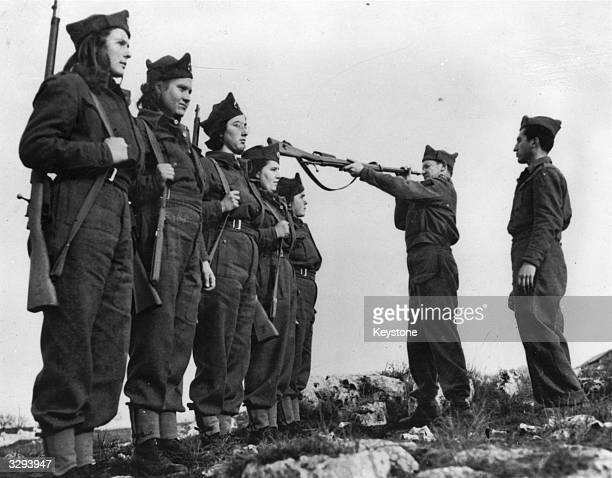 Commander of Yugolav resistance toops inspects the rifles of a squad of women guerillas. They are some of the fiercely patriotic Yugoslavia...