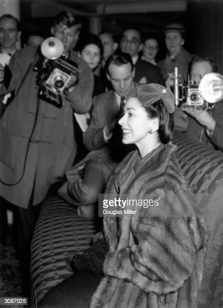 Ballerina Margot Fonteyn faces a barrage of press camera during a press call to announce her forthcoming marriage to diplomat Dr Roberto Arias