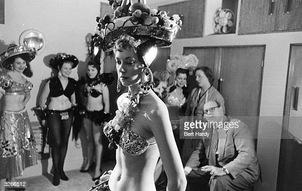 Dancers at a nightclub wearing cabaret costume with a hat covered in fruit Original Publication Picture Post 8225 The Nightclub With A Difference pub...