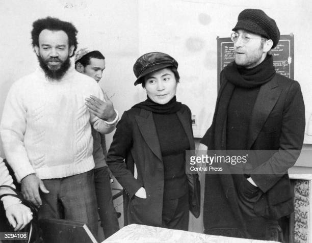 Beatle John Lennon and his wife Yoko Ono with black power leader Michael X at his house in Holloway where they exchanged a plastic bag containing...