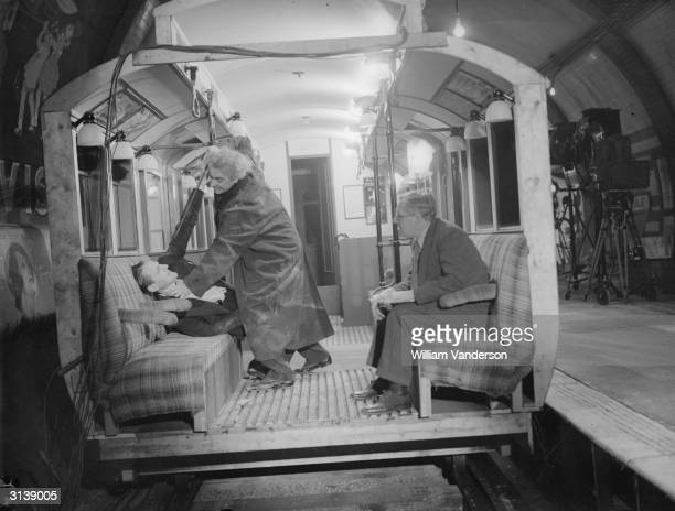On a tube train actor Ralph Richardson attacks comic actor Jack Hulbert They are being directed by Walter Forde in the Gaumont British film 'Alias...