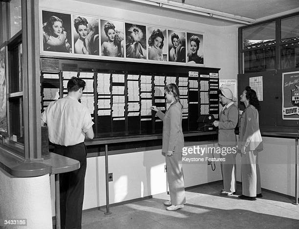 Employees of the Warner Brothers Film Studios messenger department punch their time cards beneath studio portraits of actress Martha Vickers