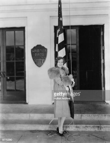 Dolores Costello the American silent screen heroine who worked for Warner Brothers She is outside the studio about to raise the flag known as 'Old...