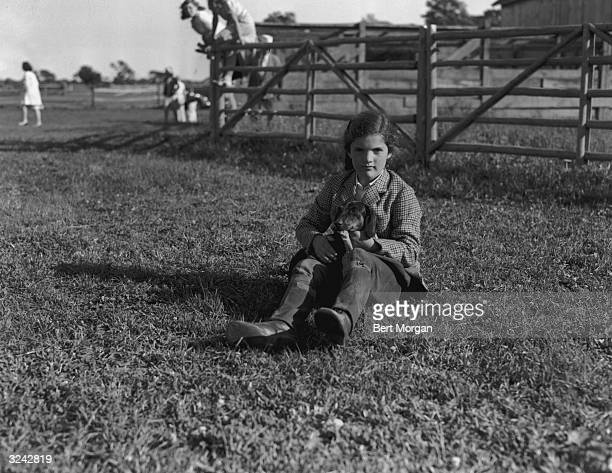 Portrait of Jacqueline Bouvier , daughter of Mr and Mrs John V Bouvier III, wearing riding clothes and sitting in a field while holding her dog,...