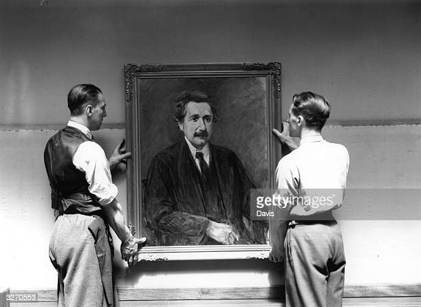 Two men prepare to hang a portrait of Albert Einstein by Max Liebermann at an exhibition of 'degenerate' German art at the New Burlington Galleries...