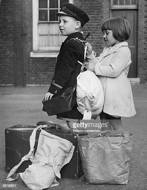 A little girl evacuee adjusts a back pack for her companion