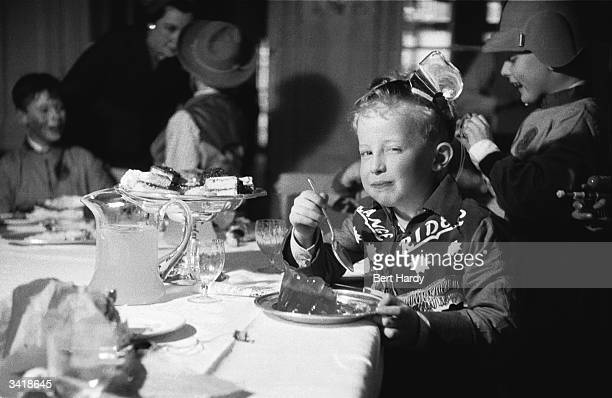 Boy dressed in a cowboy costume enjoying jelly and cakes at a party. Original Publication: Picture Post - 6578 - Cowboys Versus Spacemen - pub. 1953