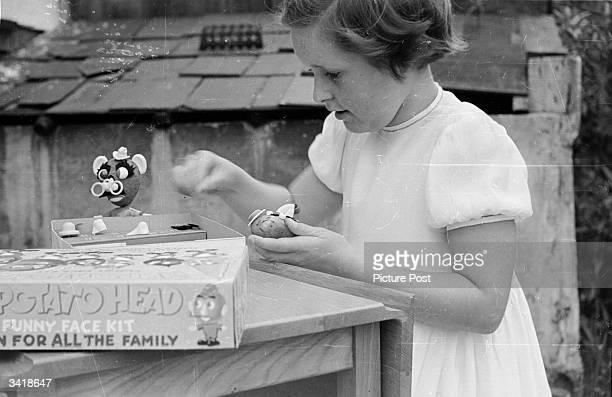 Child playing with a Mr Potato head. Original Publication: Picture Post - 6578 - Cowboys Versus Spacemen - pub. 1953