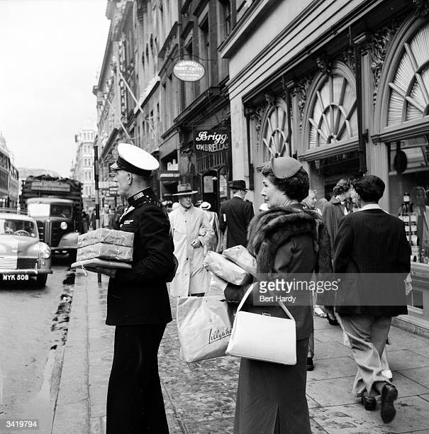 A commissionaire and a customer outside Fortnum and Mason's in Piccadilly London Original Publication Picture Post 6576 Know Your Piccadilly pub 1953