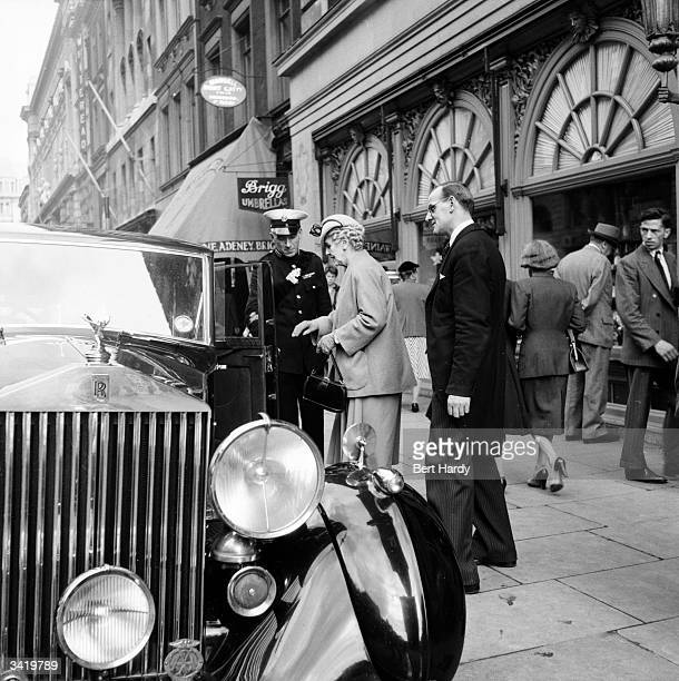 A commissionaire showing two customers to their car outside Fortnum and Mason's in Piccadilly London Original Publication Picture Post 6576 Known...