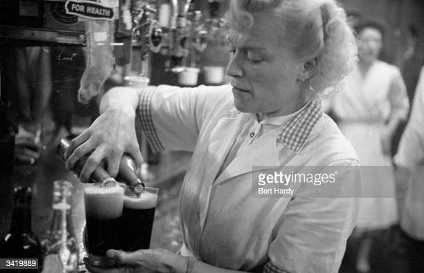 A woman at work behind a bar in the Piccadilly district of London Original Publication Picture Post 6576 Known Your Piccadilly pub 1953