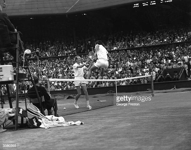 Australian tennis player Roy Emerson leaping over the net to shake hands with Fred Stolle who he has just beaten in the Wimbledon Singles...