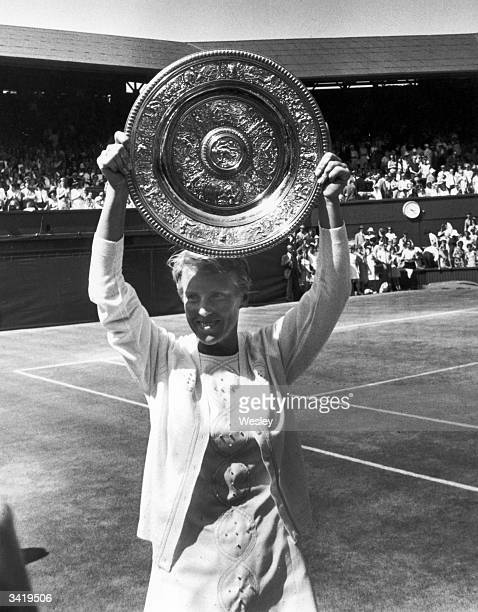 British tennis player Ann Jones holding up the trophy after beating Billie Jean King in the Ladies singles final at Wimbledon
