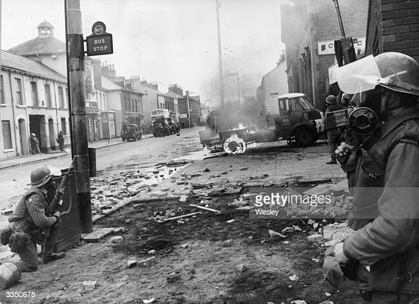 Armed British troops take up defensive positions on the Falls Road. 5 Catholics were killed, 60 injured and many homes devastated when the British...