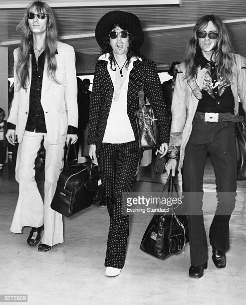 Theatrical rock singer Alice Cooper centre and friends at London airport