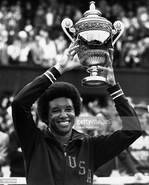 American tennis player Arthur Ashe holding aloft the trophy after beating compatriot Jimmy Connors in the men's singles finals at the Wimbledon Lawn...