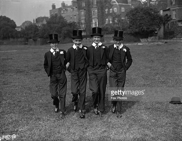 Four young boys in their Harrow school uniform sporting toppers and buttonholes