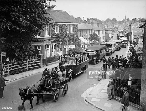 Horse and cart holds up a queue of charabancs as they drive through the streets of Epsom on their way to the Derby.