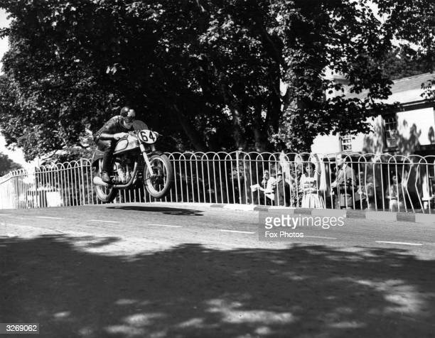 Artie Bell jumps over a humpback bridge on his Norton during the 1950 Isle of Man TT Races