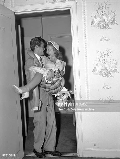 Tony Curtis carries his wife Janet Leigh over the threshold at the Waldorf after their Greenwich Ct wedding