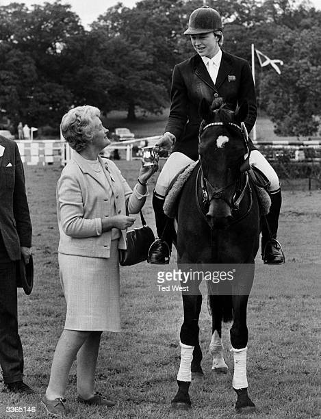 Marion Coakes World Ladies Show Jumping Champion on 'Stroller' reciving at small trophy from Mrs R Uden of W D H O Will for winning the Wills Grand...