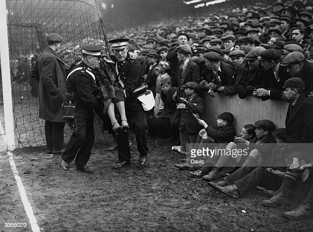 An injured spectator is removed from the crowd during a sixth round FA Cup clash between West Ham United and Birmingham City at Upton Park