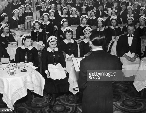 Waitresses known as Nippies at Lyon's Corner House in London receiving their instructions at the start of the day