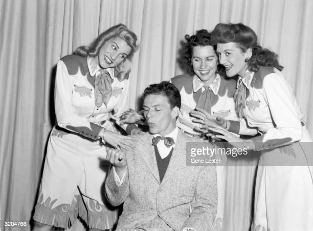 EXCLUSIVE American singer and actor Frank Sinatra looks at his finger nails and whistles while the Andrews Sisters stand over him and sing in front...