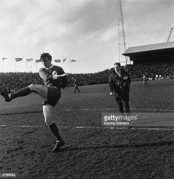 Liverpool football player Tommy Smith in action followed by a photographer.