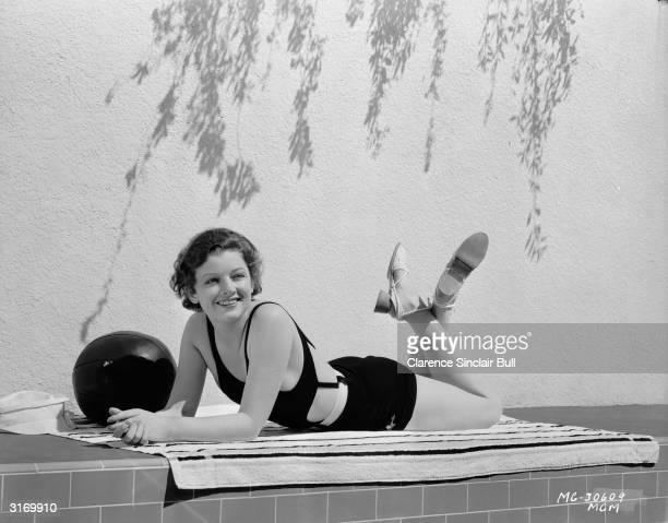 American actress Myrna Loy enjoying a spot of sunbathing