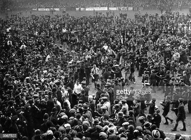 Football players are shepherded off by police as the crowd runs on to the pitch after the match between Brentford and Sheffield United at Brentford