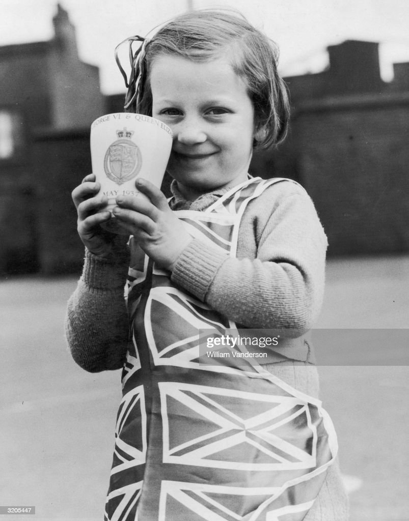 A pupil at Essex Street Infants School in east London with her Coronation gift mug, given to the children by London County Council to mark the coronation of King George VI.