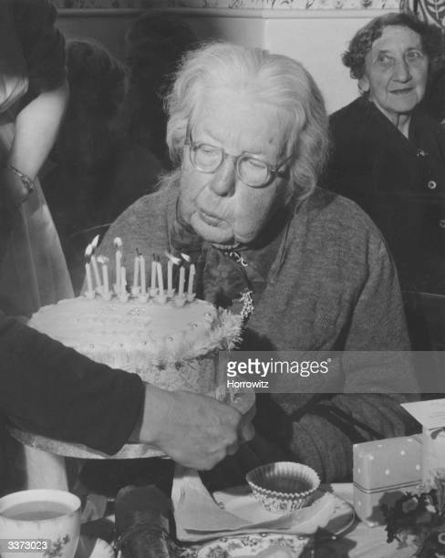 Miss Mary Huntley of North Kensington London blowing out candles on her birthday cake to celebrate her 99th birthday Her sister lived to be a 100