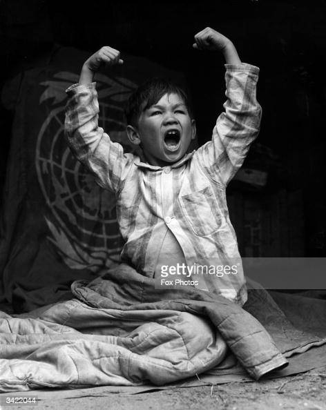 A 9 year-old Chinese boy stretching and yawning as he wakes up at