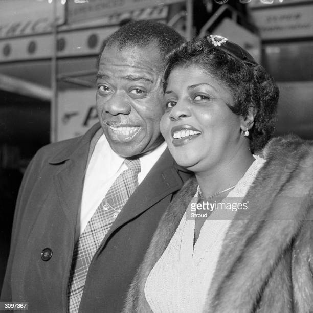 American jazz trumpeter and singer Louis Armstrong with his wife at London airport