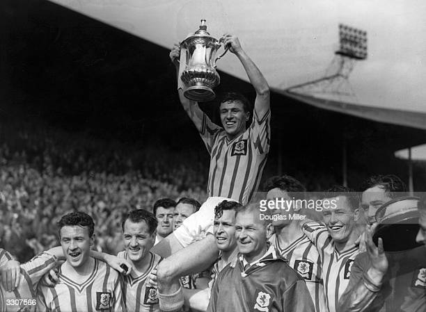 Aston Villa captain J Dixon lifts the FA Cup trophy as he is carried on the shoulders of his teammates after their 21 win over Manchester United in...