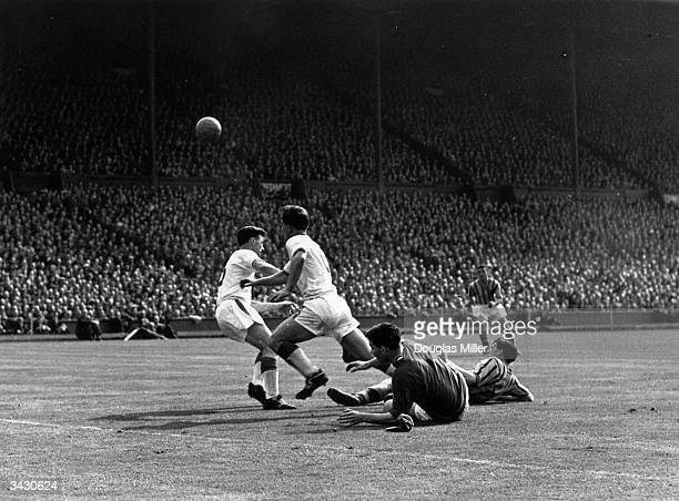 Manchester United footballers Duncan Edwards and Roger Byrne trying to stop an Aston Villa footballer scoring during the FA Cup final.