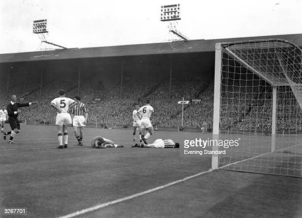 Peter McParland of Aston Villa lies injured in the goal area alongside goalkeeper Ray Wood of Manchester United after their sixth minute collision...