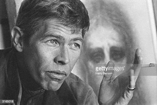 American actor James Coburn sitting in front of a drawing of Christ by American actress Kim Novak