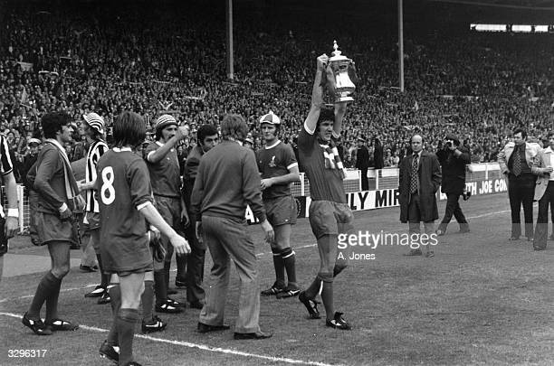 Liverpool Captain Emlyn Hughes holds the FA Cup aloft in victoryafter hsi side's 30 defeat of Newcastle United in the FA Cup final at Wembley Stadium