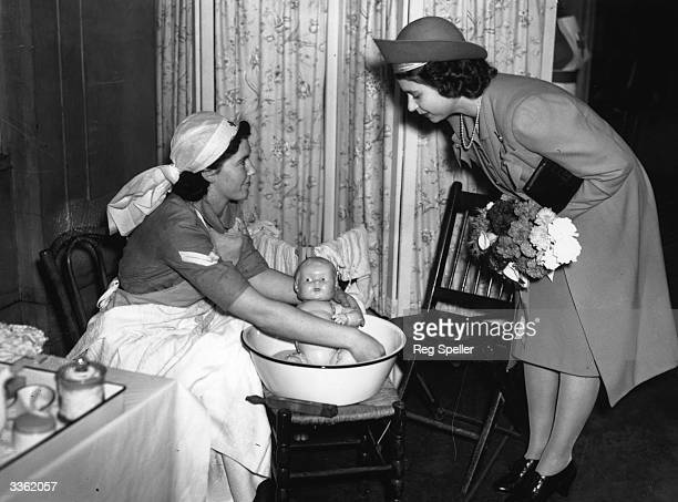 Princess Elizabeth watching a Red Cross Nurse demonstrating how to bath a baby at a conference of Red Cross Youth Members at Friends' House Euston...