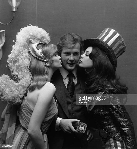 British actor Roger Moore receives kisses from Miss United Kingdom Marilyn Ann Ward and Miss United States Brucene Smith after presenting them with...