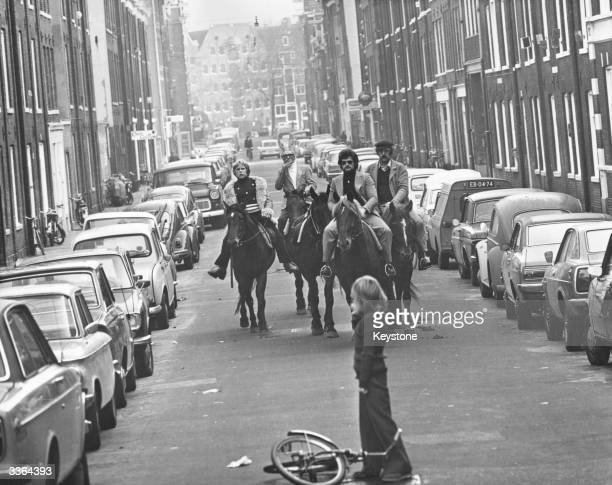 Four horsemen riding through the streets of Amsterdam on a 'motorless day' when cars are prohibited due to the oil crisis in the Middle East