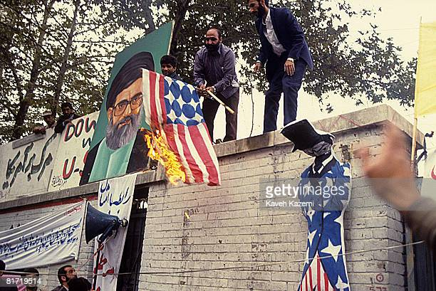 Iranian Revolutionary Guards burn a homemade US flag on top of the walls of the former US embassy in Tehran on the anniversary of its occupation by...