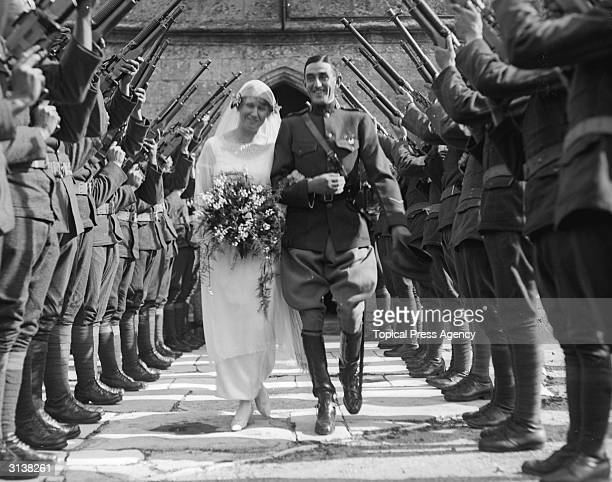 Lt Col Mitchell and his bride Matilda Vickers walk under a guard of honour formed by soldiers holding guns in the air