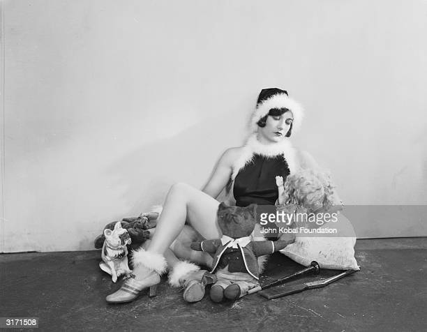 American actress Joan Crawford wearing a festive outfit and surrounded by soft toys