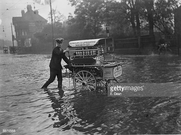 A milkman pushes his milkfloat through a flooded street in Edmonton London after torrential rain disrupted traffic