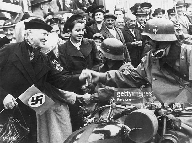 Ethnic Germans living in the Sudetenland in Czechoslovakia welcome the German troops who have arrived to annex the region under the terms of the...